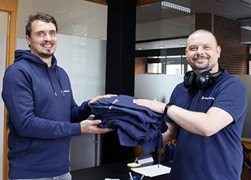Wieland begrüßt Oliver bei Exabyters und stattet ihn mit entsprechender blauer Kleidung aus
